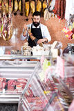 Male shop assistant demonstrating jamon Stock Photos