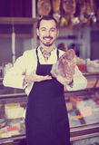 Male shop assistant demonstrating piece of meat in butcher's s. Smiling american male shop assistant demonstrating piece of meat in butcher's shop Royalty Free Stock Image