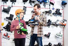 Male shop assistant helping boy to choose roller-skates in sport Stock Photos