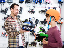 Male shop assistant helping boy to choose roller-skates in sport Royalty Free Stock Photo