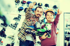 Male shop assistant helping boy to choose roller-skates in sport Stock Image