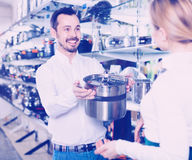 Male shop assistant helping customer to choose saucepan Stock Photos
