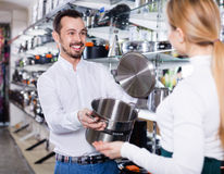 Male shop assistant helping customer to choose saucepan Royalty Free Stock Image