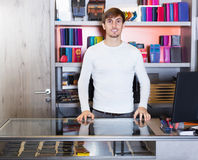 Male shop assistant in wallet section. Male shop assistant posing near glass display in wallet section Royalty Free Stock Photo