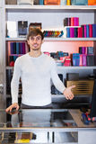 Male shop assistant in wallet section. Smiling male shop assistant posing near glass display in wallet section Royalty Free Stock Images