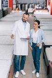 Male shop assistant in white coat with notebook helping woman. In choosing mattress in furniture shop Royalty Free Stock Photos