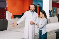 male shop assistant in white coat showing goods to customer stock photos