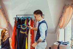 Male shop assistant and young woman in the fashion boutique. Male shop assistant and young women choosing evening dress in the fashion boutique. Fashion business Royalty Free Stock Photography