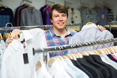 Male in the shop choosing shirts. Happy male in the shop choosing shirts Stock Photography