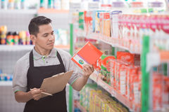 Male shopkeeper checking the product. Male shopkeeper checking the quality of the product at supermarket Royalty Free Stock Image