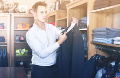 Male shopper choosing new suit in male shop Stock Images
