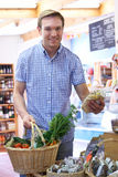 Male Shopper In Delicatessen Buying Organic Produce. Man Shopping In Delicatessen For Organic Produce Royalty Free Stock Photo