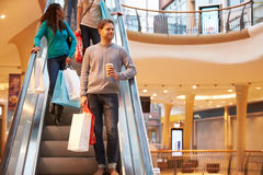 Male Shopper On Escalator In Shopping Mall. Holding Hot Drink And Shopping Bags Stock Image