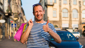 Male shopper holding shopping bags looking very happy.  Royalty Free Stock Photos