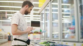 Young man is examining pack with frozen vegetables in a hall of supermarket stock video footage