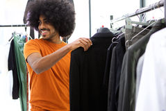 Male shopper looking for clothes. Smiling male shopper looking for clothes Stock Photography