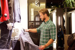 Male shopper looking at clothes in store. Portrait of a male shopper looking at clothes in store Stock Photos