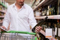 Male Shopper Looking at Liquor Bottle. Young male shopper looking at liquor bottle at supermarket Stock Photos