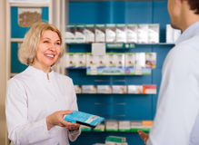 Male shopper with mature woman pharmacist. Male shopper with mature women pharmacist near counter in drugstore Stock Photography