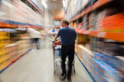 Male shopper in store with shopping cart. Male shopper in large store with shopping cart; blurred image to imply motion, action and stress Royalty Free Stock Photography