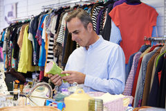 Male Shopper In Thrift Store Looking At Ornaments. Male Shopping In Thrift Store Looking At Ornaments Royalty Free Stock Photo