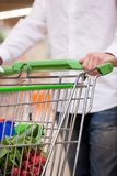 Male Shopper with Trolley at Supermarket. Cropped image of man shopping groceries for house Royalty Free Stock Images