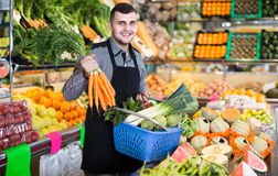 Male shopping assistant helping to buy fruit and vegetables in g. Happy male shopping assistant helping to buy fruit and vegetables in grocery shop Stock Photography