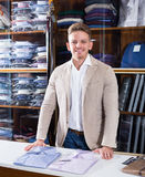 Male shopping assistant offering various shirts. In men's cloths store Stock Images