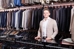 Male shopping assistant offering various suits in men's cloths. Happy american male shopping assistant offering various suits in men's cloths store Royalty Free Stock Image