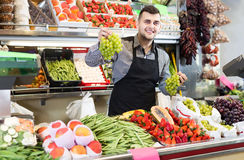 Male shopping assistant weighing grapes in grocery shop. Happy american male shopping assistant weighing grapes in grocery shop Stock Image