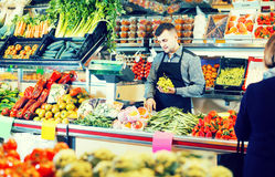 Male shopping assistant weighing grapes in grocery shop. Happy european male shopping assistant weighing grapes in grocery shop Stock Image