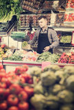 Male shopping assistant weighing grapes in grocery shop. Happy spanish male shopping assistant weighing grapes in grocery shop Royalty Free Stock Photo