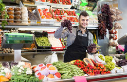Male shopping assistant weighing grapes in grocery shop. Smiling american male shopping assistant weighing grapes in grocery shop Stock Images
