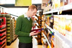 Male Shopping Comparing Products. A male shopper in a grocery store comparing products Royalty Free Stock Photos