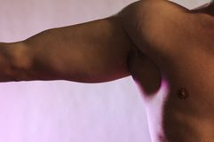 Male shoulder muscle. On lavender background arm extended strait to the side Royalty Free Stock Photos