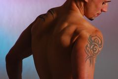 Male with shoulder tattoo. Male looking down shirtless with a tribal tattoo  on  his shoulder Royalty Free Stock Photos