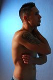 Male with shoulder tattoo blue. Male looking down shirtless with a tribal tattoo  on  his shoulder Stock Photo