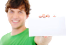 Male showing blank white card on foreground. Soft focus Royalty Free Stock Images