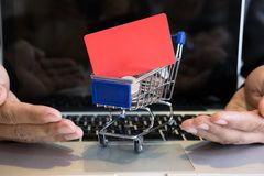 Male showing a credit card in mini supermarket cart trolley full Stock Photo