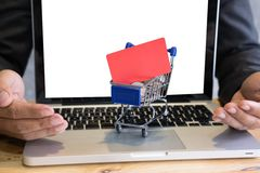 Male showing a credit card in mini supermarket cart trolley full. Young male showing a credit card in mini supermarket cart trolley full of coins on laptop Stock Photography