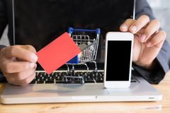 Male showing a credit card and mobile smart phone with supermark. Young male showing a credit card and mobile smart phone with supermarket cart trolley on laptop Royalty Free Stock Image