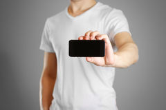 Male shows a black phone. Holding it horizontally. Isolated.  Royalty Free Stock Photography