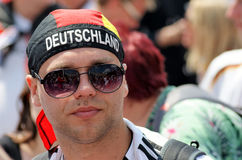 A male shows off his German pride. The colors of the German flag and the name `Deutschland` on the mans head scarf shows his pride in the country.  He is in a Stock Image