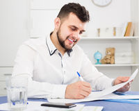 Male signing agreement papers about finances at home. Young male signing agreement papers about finances at home Royalty Free Stock Photos
