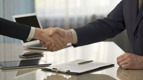 Male signing business agreement, shaking hands with partner, partnership, deal