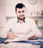 Male signing  papers about financial agreement. Smiling male signing  papers about financial agreement at home Royalty Free Stock Images