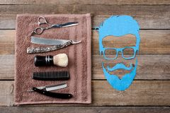 Male silhouette and barber towel. Comb, straight raizors, a brush and scissors on a barber towel, close-up. Man face silhouette on the wooden background. Art of Royalty Free Stock Photography