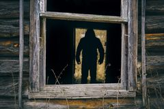 Male silhouette in the doorway of abandoned house. Dark male silhouette standing in the doorway of abandoned house. View through the broken window Stock Photos