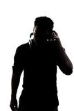 Male in silhouette listening to headphones. Isolated on white background Royalty Free Stock Photography