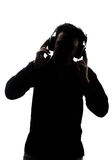 Male in silhouette listening to headphones. Isolated on white background Stock Photography